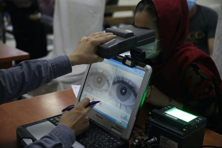 A computer screen shows an enlarged image of a pair of eyes as an arm holds a boxlike object in front of the eyes of a woman wearing a headscarf and facemask