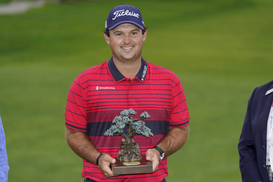 Patrick Reed stands on the South Course while holding his trophy for winning the Farmers Insurance Open golf tournament at Torrey Pines, Sunday, Jan. 31, 2021, in San Diego. (AP Photo/Gregory Bull)