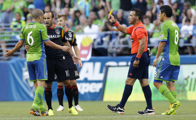 Los Angeles Galaxy's Landon Donovan, second from left, is booked with a yellow card by referee Hilario Grajeda, second from right, after Donovan fouled Seattle Sounders' Osvaldo Alonso, left, in the first half of an MLS soccer match, Monday, July 28, 2014, in Seattle. (AP Photo/Ted S. Warren)