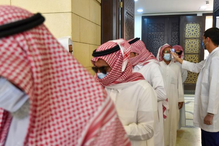A Saudi medical worker checks the temperatures of worshippers upon their arrival at Al-Rajhi mosque on Sunday