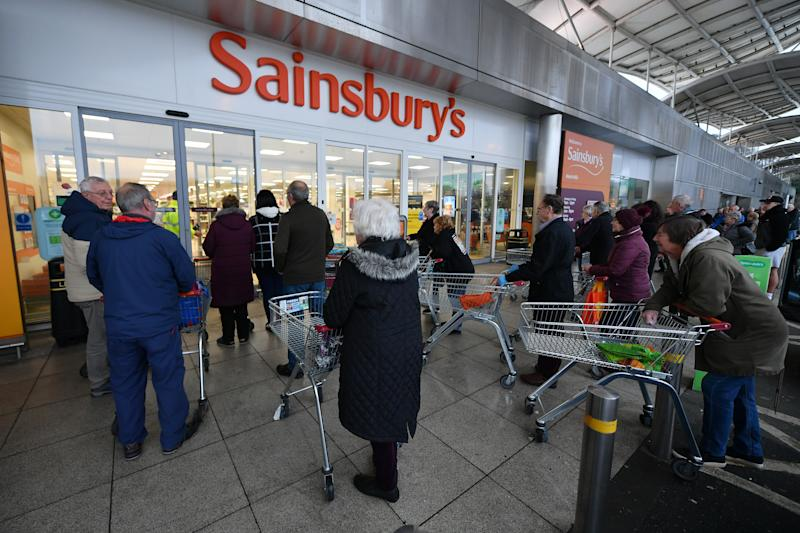 "PLYMOUTH, UNITED KINGDOM - MARCH 19: Shoppers queue outside a Sainsbury's supermarket prior to opening in Plymouth on March 19, 2020 in Plymouth, United Kingdom. The store allowed only the elderly and vulnerable into the store for the first hour. After spates of ""panic buying"" cleared supermarket shelves of items like toilet paper and cleaning products, stores across the UK have introduced limits on purchases during the COVID-19 pandemic. Some have also created special time slots for the elderly and other shoppers vulnerable to the new coronavirus. (Photo by Dan Mullan/Getty Images)"