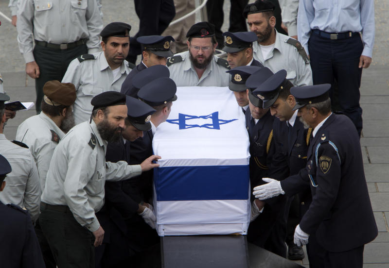 Members of the Knesset guard carry the coffin of former Israeli Prime Minister Ariel Sharon at the Knesset plaza, in Jerusalem, Sunday, Jan. 12, 2014. Sharon, the hard-charging Israeli general and prime minister who was admired and hated for his battlefield exploits and ambitions to reshape the Middle East, died Saturday, eight years after a stroke left him in a coma from which he never awoke. He was 85. (AP Photo/Oded Balilty)
