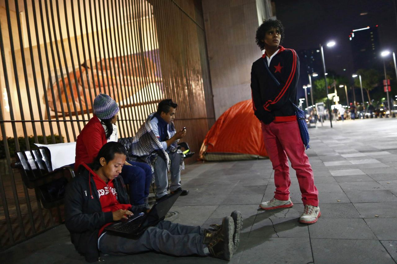 REFILE - CORRECTING HEADLINE  Migrants from Central America prepare to stay overnight during a protest demanding a reform in U.S. immigration laws which regulate the illegal exodus of children into the U.S., and to provide protection for them, outside the Foreign Affairs building in Mexico City August 9, 2014. A recent surge in migrant children from Central America across the U.S. border has eased, but the numbers are still high compared to historical standards, and could rise again once the weather cools down, the White House said on Friday. REUTERS/Edgard Garrido (MEXICO - Tags: SOCIETY IMMIGRATION POLITICS CIVIL UNREST)