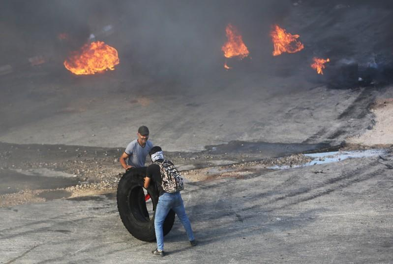Demonstrators push a tire to be set on fire during a protest targeting the government over an economic crisis, in Nabatiyeh