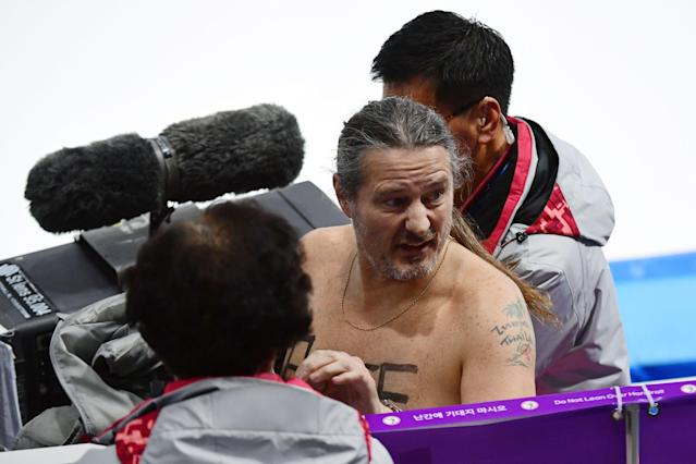 <p>A shirtless man clad in a tutu is escorted off the rink following the men's 1,000m speed skating event medal ceremony during the Pyeongchang 2018 Winter Olympic Games at the Gangneung Oval in Gangneung on February 23, 2018. / AFP PHOTO / Roberto SCHMIDT </p>