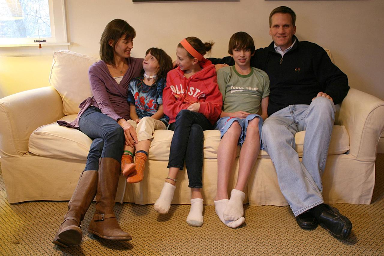 "In this Feb. 22, 2012 photo, Clara Beatty, second from left, looks at her mother, Janet Beatty, as the family poses for a family photo in their Winnetka, Ill., home. From center to left are Clara's older siblings, Gretchen and Henry, and her father Eric Beatty. Her parents discovered Clara was quite able to cope, sometimes better than they. Even today, her mother, Janet Beatty, is astounded at how well her youngest daughter navigates the world. ""Even when she was little, you could look at her and people would say there's an old soul in there,"" she says. ""She just had these big eyes and you could see her taking everything in."" (AP Photo/Martha Irvine)"