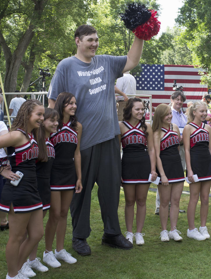 Seven-foot, eight-inch tall, Igor Vovkovinskiy, the self proclaimed biggest supporter of President Barack Obama, takes a photo with cheerleaders from the Cannon Falls high school prior to a town hall event at Lower Hannah's Bend Park, in Cannon Falls, Minn., Monday, Aug. 15, 2011. The President is on a three-day Midwestern bus tour. (AP Photo/Nati Harnik)
