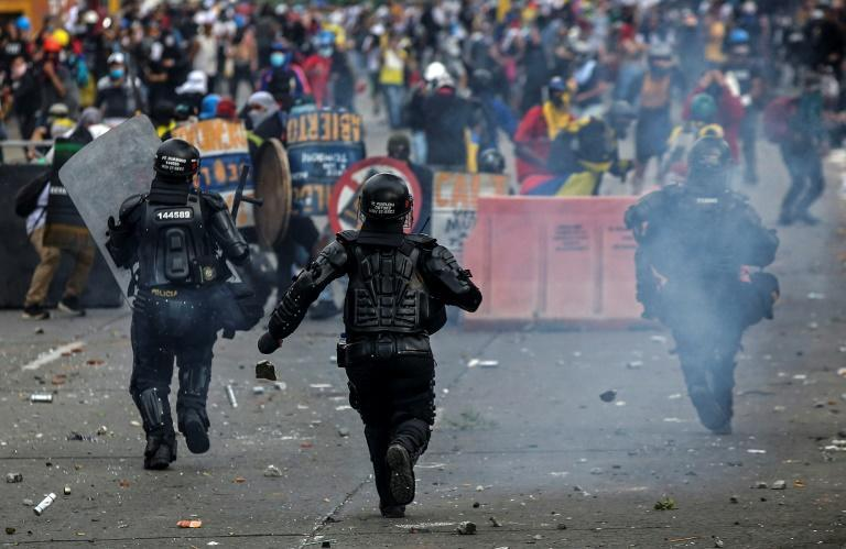 Clashes between riot police and demonstrators, some armed with machetes, left dozens of civilians injured in the cities of Medellin and Cali