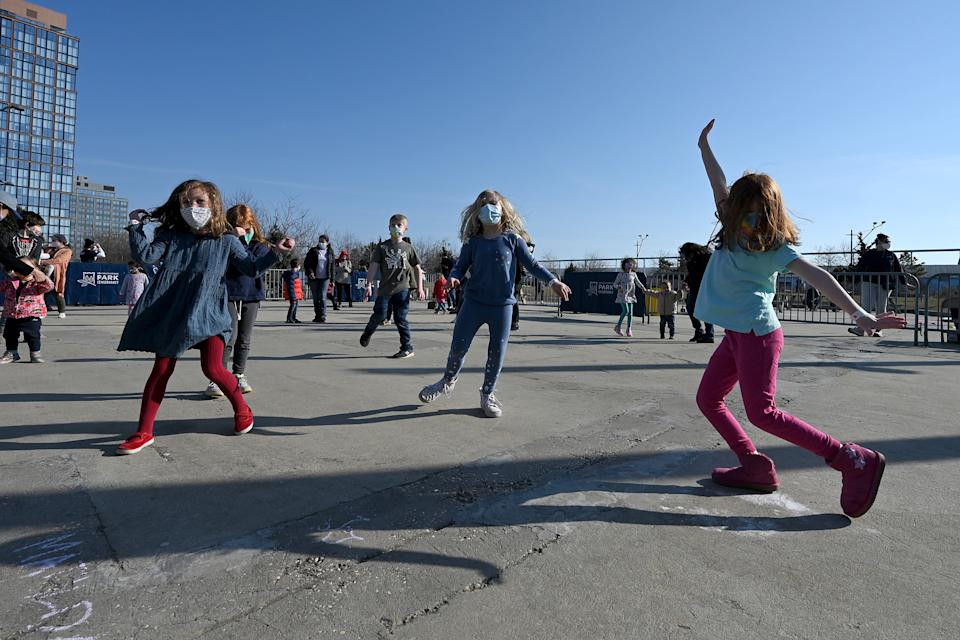 Children and parents dance to a DJ spinning kid-friendly music on a rooftop in NYC as they are wear masks and maintain social distance. Source: AAP