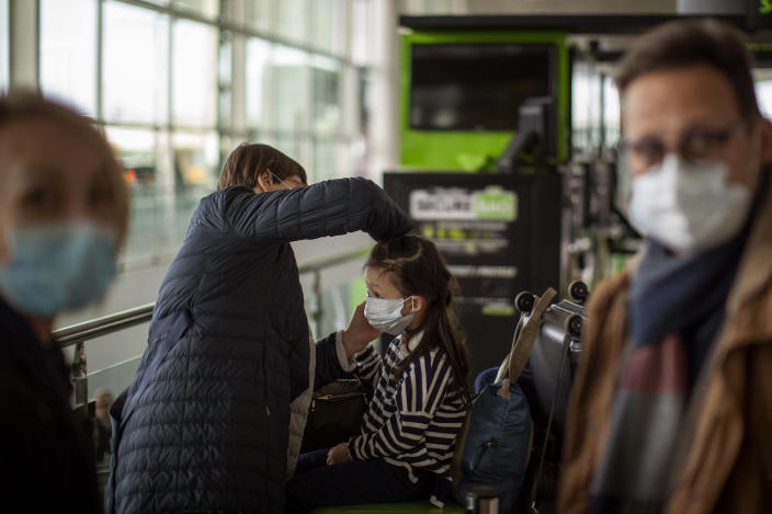 A woman fixes a mask to a child at Barcelona airport on Thursday. (Emilio Morenatti/AP)
