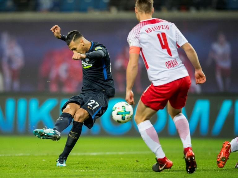 Berlin's forward Davie Selke (L) shoots to score the first goal next to Leipzig's defender Willi Orban during the German first division Bundesliga football match December 17, 2017