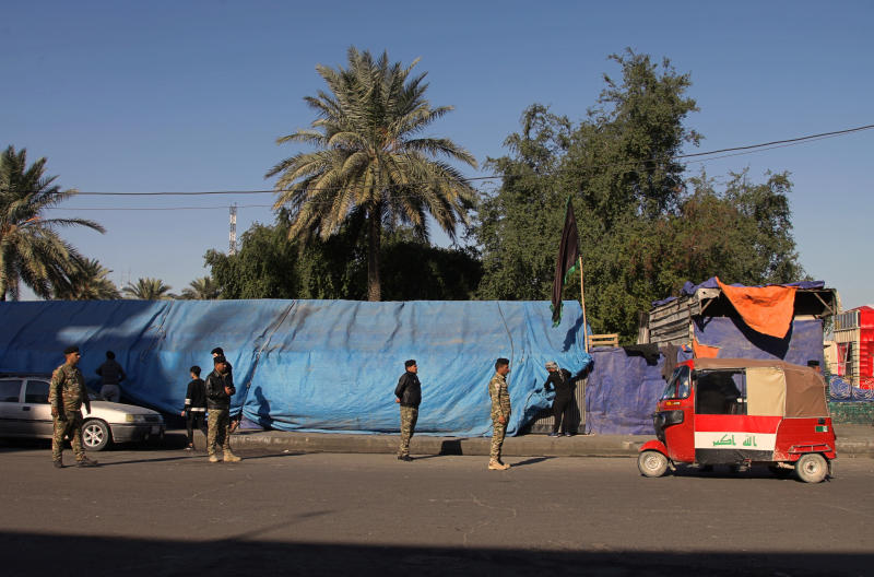 Iraqi security forces stand guard outside Tahrir Square where ongoing anti-government protests are taking place, in Baghdad, Iraq, Tuesday, Dec. 24, 2019. (AP Photo/Khalid Mohammed)