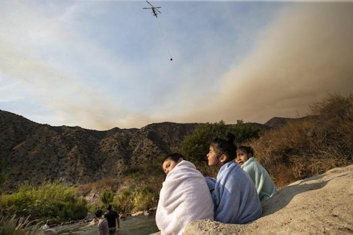 "The Ranch2 fire burns nearby as Carlos Alvarado, 5, Shanti Mata, 6, and Aliah Alvarado, 6, dry off while swimming with others near a drainage pipe along the San Gabriel River Aug. 16. <span class=""copyright"">(Robert Gauthier / Los Angeles Times)</span>"