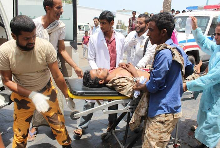 Yemeni emergency personnel carry an injured man following a bomb attack that targeted Yemeni forces in Aden's Khormaksar district (AFP Photo/Saleh al-Obeidi)