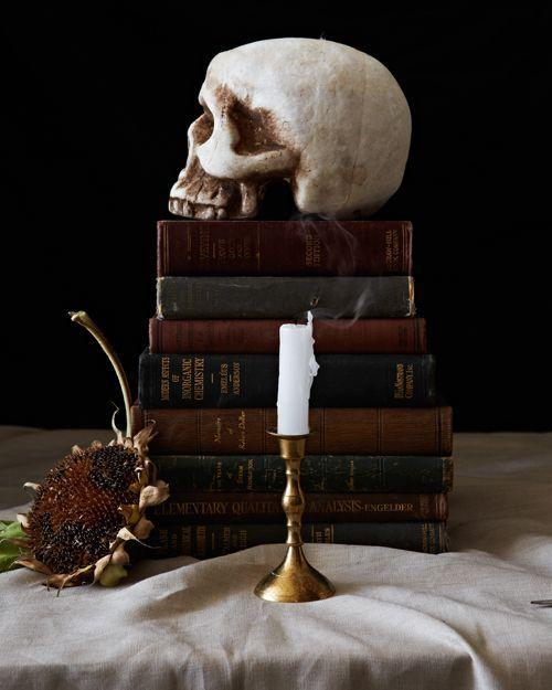 """<p>Use a skull, stacked vintage books, and candlesticks to make your table look straight out of a pre-millennium still-life. </p><p><strong>Get the tutorial at <a href=""""https://thehousethatlarsbuilt.com/2014/10/decor-for-your-halloween-party.html/"""" rel=""""nofollow noopener"""" target=""""_blank"""" data-ylk=""""slk:The House That Lars Built"""" class=""""link rapid-noclick-resp"""">The House That Lars Built</a>. </strong> </p>"""