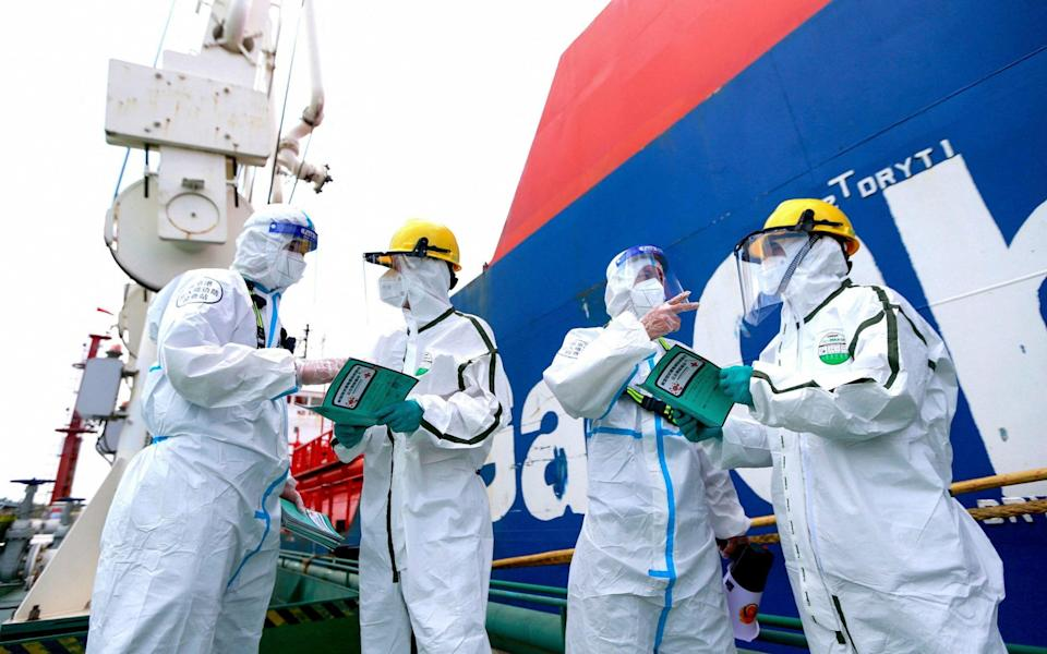 Police officers (L and 2nd R) wearing protective gear explain pandemic prevention information to fight against the spread of Covid-19 coronavirus to workers at Nanjing port in China's eastern Jiangsu province - STR/AFP/Getty