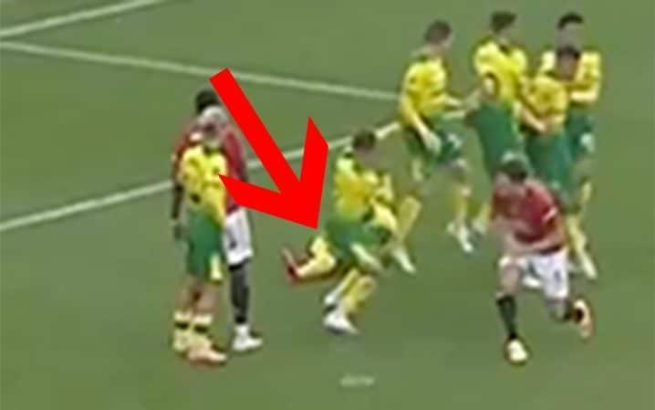 Norwich defender on ground behind wall