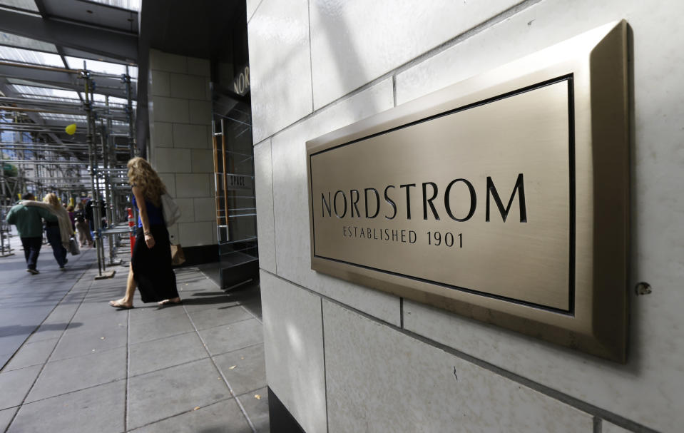 FILE- In this Sept. 13, 2017, file photo, shoppers come and go from Nordstrom Inc.'s flagship store in downtown Seattle. Nordstrom offered on Thursday, Feb. 4, 2021, a snapshot of its holiday 2020 performance that underscored the challenges ahead as they navigate a pandemic. Upscale Nordstrom reiterated its guidance for the fiscal holiday quarter, saying it expects to see a drop in total sales in the low 20% range compared to the year-ago period. (AP Photo/Ted S. Warren, File)