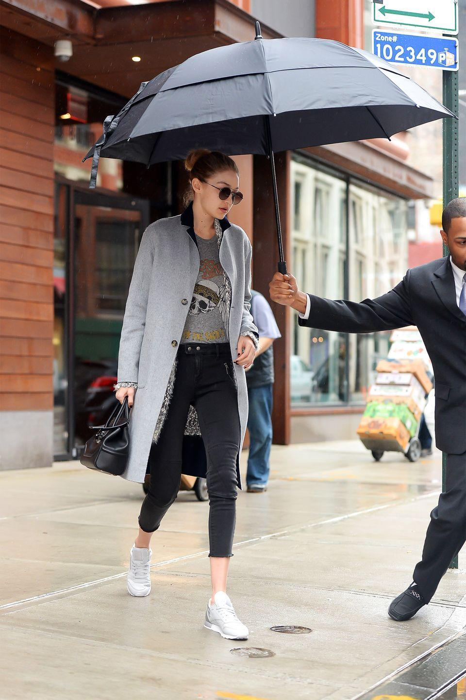 <p>In a grey peacoat, grey knit sweater, Lauren Moshi graphic tank, cropped black jeans, white Reebok sneakers, round sunglasses and a black leather handbag while out in New York.</p>