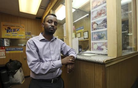 Shakir Hussein stands at the counter of his money transfer business Mustaqbal Express in Minneapolis June 23, 2014. REUTERS/Eric Miller