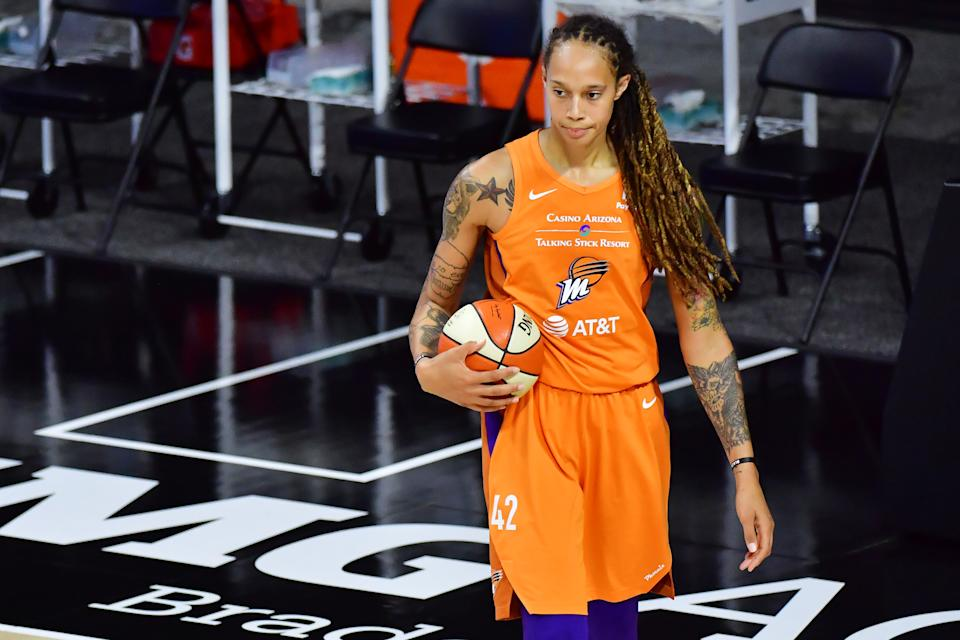 Brittney Griner holds a basketball while in an orange Mercury uniform.