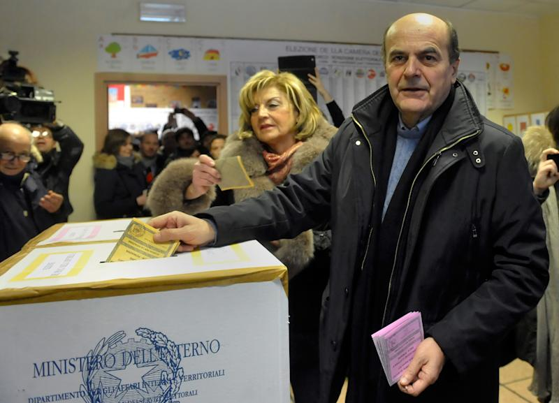 Pier Luigi Bersani, right, leader of the Democratic Party, casts his ballot with his wife Daniela, in Piacenza, Italy, Sunday, Feb. 24, 2013. Italy votes in a watershed parliamentary election Sunday and Monday that could shape the future of one of Europe's biggest economies. (AP Photo/Marco Vasini)