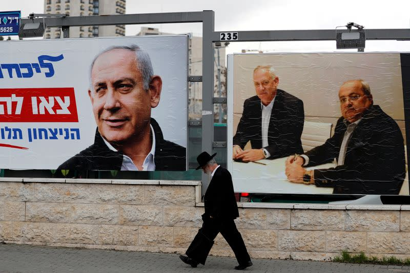 FILE PHOTO: An ultra-Orthodox Jewish man walks next to Likud party election campaign banners in Jerusalem