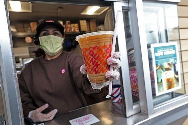 PHOTO: A Dunkin' worker hands a coffee out of a drive-thru window wearing gloves and a mask as the Coronavirus continues to spread on March 17, 2020 in Norwell, Massachusetts. (Medianews Group/Digital First Media via Getty Images)