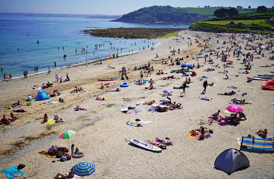 People enjoy the sunshine on Gyllyngvase Beach near Falmouth in Cornwall (Aaron Chown/PA) (PA Wire)