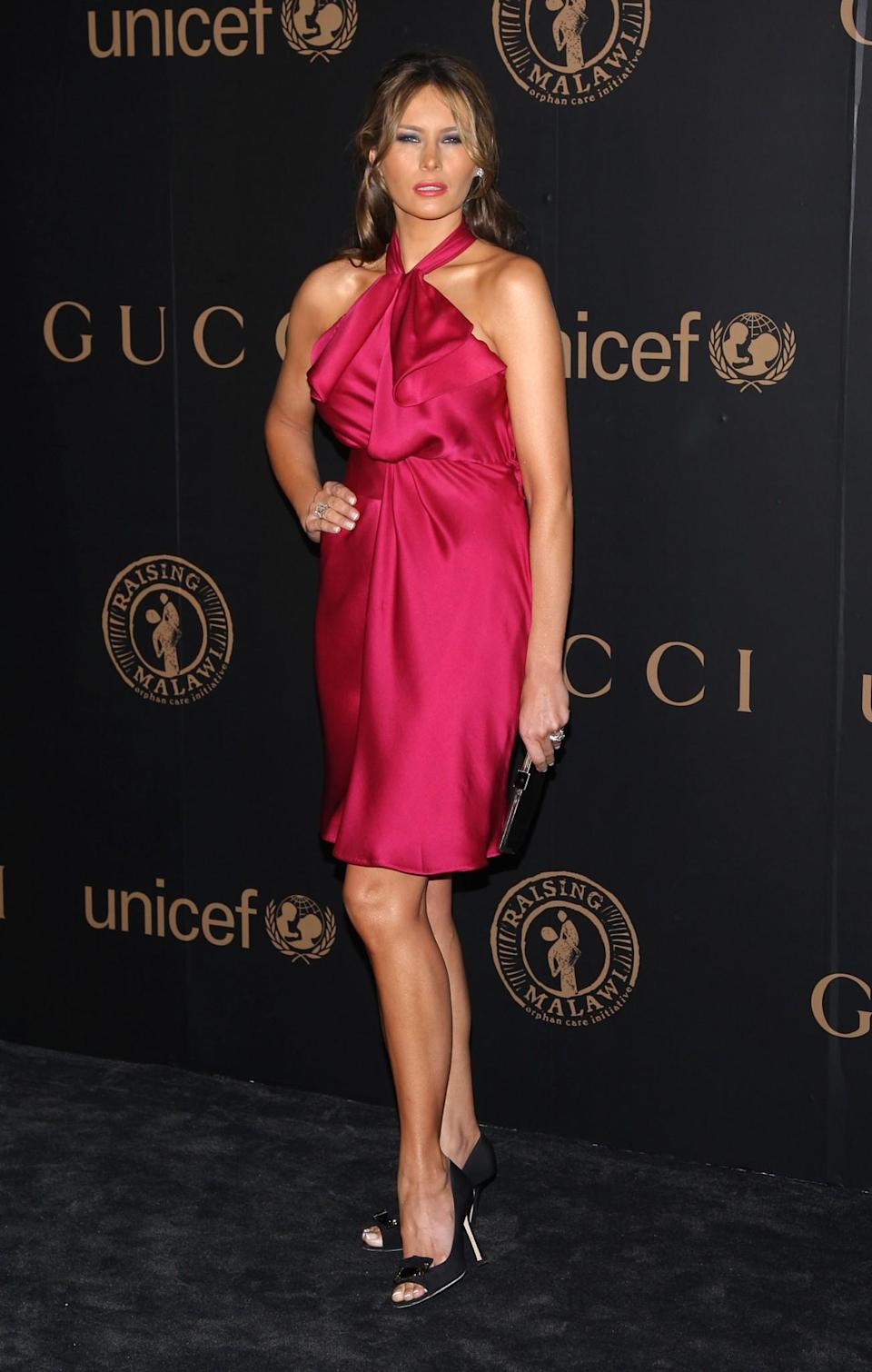 <p>One of Melania's favourite shades, this hot pink halterneck dress worn to a Gucci party caught the attention of the paparazzi. <i>[Photo: Getty]</i> </p>