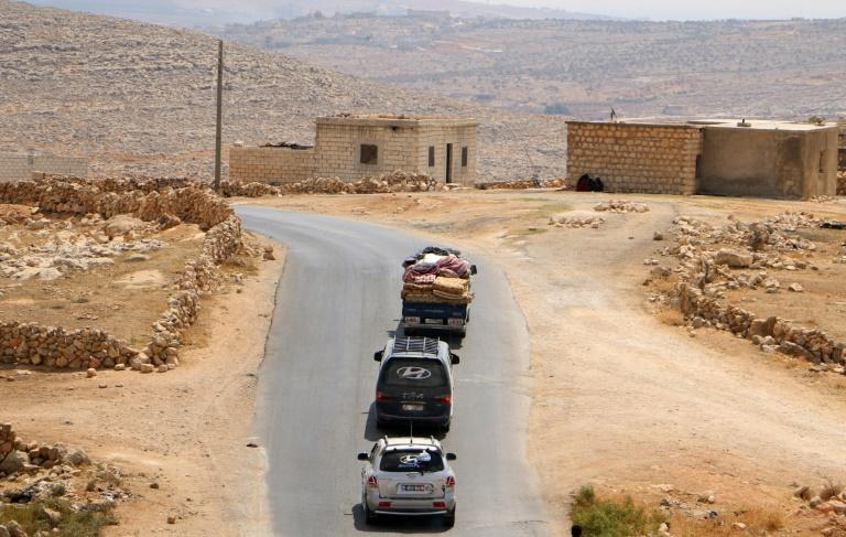 Displaced Syrians fleeing regime and Russian air strikes ride in vehicles with their belongings near a camp in Kafr Lusin close to the border with Turkey