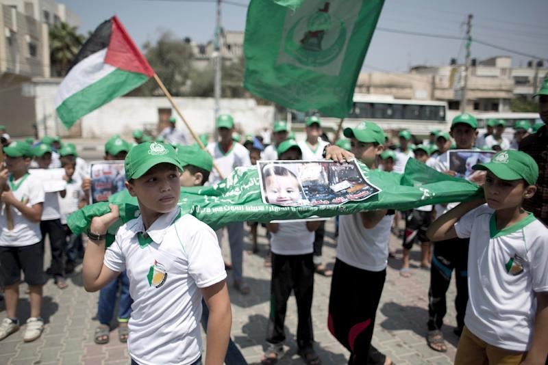 Palestinian children carry a funeral stretcher with a picture of 18-month-old Ali Saad Dawabsha, the toddler who was burned to death by suspected Jewish extremists, during a protest in Khan Yunis in the southern Gaza Strip on August 1, 2015 (AFP Photo/Said Khatib)