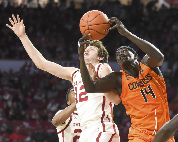 Oklahoma St forward Yor Anei (14) tries to get to the ball before Oklahoma guard Austin Reaves (12) during the first half of an NCAA college basketball game in Norman, Okla., Saturday, Feb. 1, 2020. (AP Photo/Kyle Phillips)