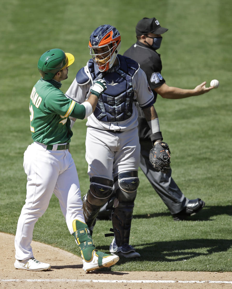 Oakland Athletics' Ramon Laureano, left, speaks with Houston Astros catcher Martin Maldonado after being hit by a pitch thrown by Astro's Humberto Castellanos in the seventh inning of a baseball game Sunday, Aug. 9, 2020, in Oakland, Calif. (AP Photo/Ben Margot)