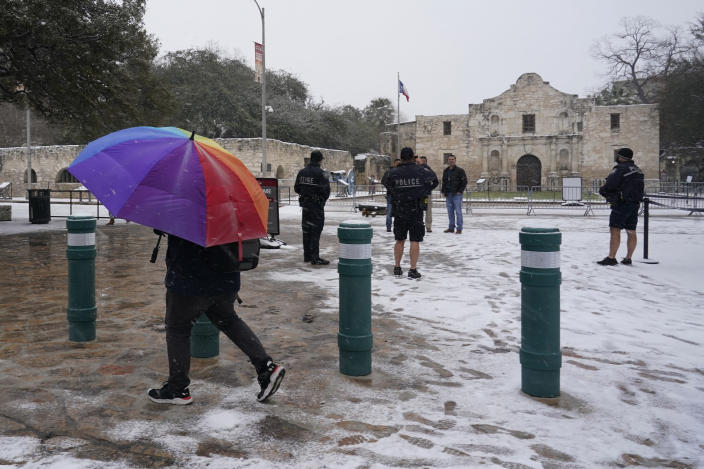 Snow begins to accumulate as San Antonio police officers gather near the Alamo, Thursday, Feb. 18, 2021, in downtown San Antonio. Snow, ice and sub-freezing weather continue to wreak havoc on the state's power grid and utilities. (AP Photo/Eric Gay)