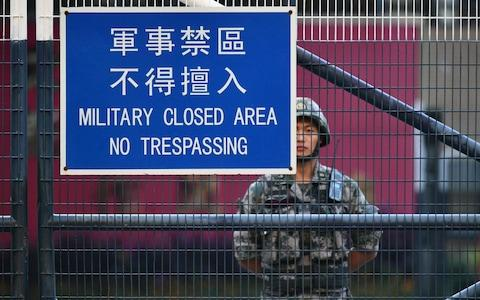 """<span>A member of Chinas People's Liberation Army (PLA) stands guard inside Osborn Barracks in Kowloon Tong in Hong Kong on November 16, 2019. - China's President Xi Jinping warned on November 14 that protests in Hong Kong threaten the """"one country, two systems"""" principle governing the semi-autonomous city that has tipped into worsening violence with two dead in a week.</span> <span>Credit: AFP </span>"""