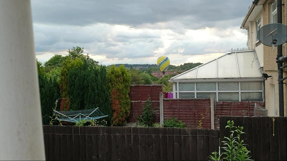 The yellow and blue balloon had to suddenly land due to strong winds. (SWNS)