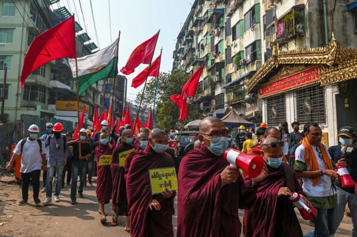 Buddhist monks and demonstrators rally against the military coup and to show their support to local residents after riot police officers used teargas to disperse a crowd that held a protest the night before in Yangon's Tamwe neighborhood