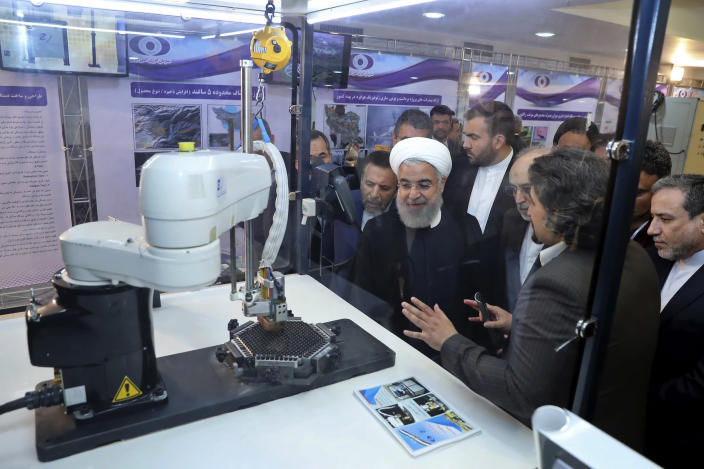 """FILE - In this April 9, 2018, file photo, released by an official website of the office of the Iranian Presidency, President Hassan Rouhani listens to explanations on new nuclear achievements at a ceremony to mark """"National Nuclear Day,"""" in Tehran, Iran. Iranian Foreign Minister Mohammad Javad Zarif acknowledged Monday, July 1, 2019, Iran had broken the limit set on its stockpile of low-enriched uranium by the 2015 nuclear deal, marking its first major departure from the unraveling agreement a year after the U.S. unilaterally withdrew from the accord. (Iranian Presidency Office via AP)"""
