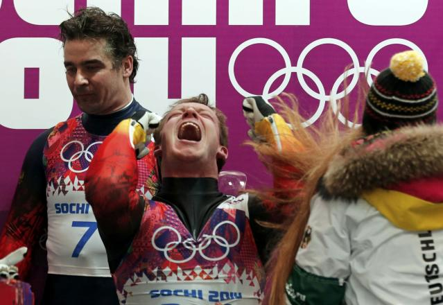 Winner Germany's Felix Loch (C) celebrates while second-placed Russia's Albert Demchenko (L) stands beside him after the men's singles luge competition at the 2014 Sochi Winter Olympics February 9, 2014. REUTERS/Murad Sezer (RUSSIA - Tags: OLYMPICS SPORT LUGE TPX IMAGES OF THE DAY)