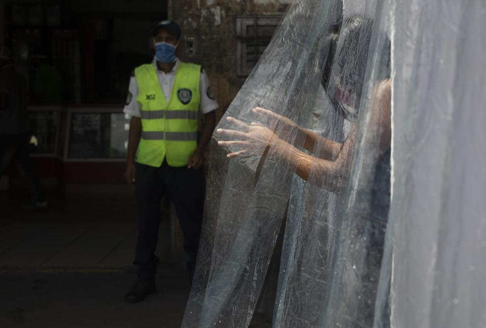 A woman wearing a protective face mask walks through a decontamination chamber as a preventive measure against the spread of the new coronavirus in the neighborhood of Petare in Caracas, Venezuela, Wednesday, July 15, 2020. (AP Photo/Ariana Cubillos)