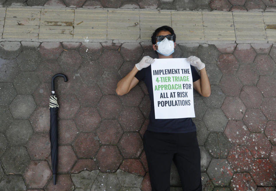 A protesters lies on the ground demanding better handling of the COVID-19 pandemic in Kathmandu, Nepal, Saturday, June 20, 2020. Hundreds participated demanding increased testing and protesting alleged corruption by government officials while purchasing equipment and testing kits. (AP Photo/Niranjan Shrestha)