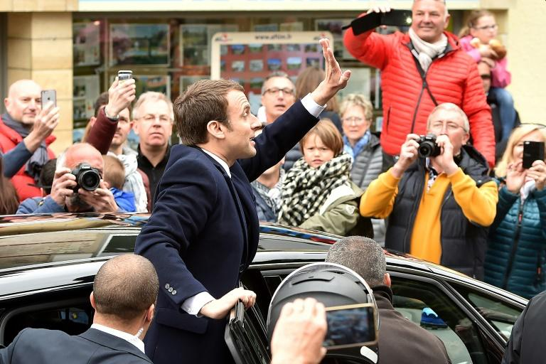 French centrist presidential candidate Emmanuel Macron greets supporters as France votes in the first round of an unpredictable election