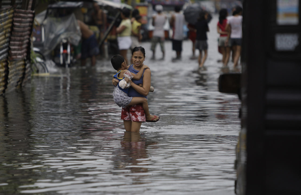 CORRECTS THE NAME OF TYPHOON IN SECOND SENTENCE - A Filipino boy holds on to his mother as they cross a flooded street brought by Typhoon Muifa in Manila, Philippines on Tuesday Aug. 2, 2011. Muifa continues to blow away from the northern Philippines after killing at least 4 people even though it did not make landfall. Classes were suspended in most parts of the metro due to floods.(AP Photo/Aaron Favila)