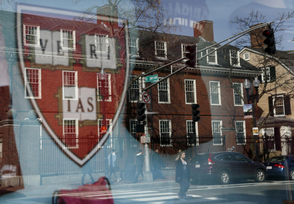 CAMBRIDGE, MA - MARCH 11:  Pedestrians are reflected in a window of a store selling Harvard paraphernalia in Cambridge, MA on March 11, 2020. A day after Harvard announced it would be sending students home for the rest of the semester due to coronavirus concerns, Harvard Square was unusually quiet.  (Photo by Jessica Rinaldi/The Boston Globe via Getty Images)