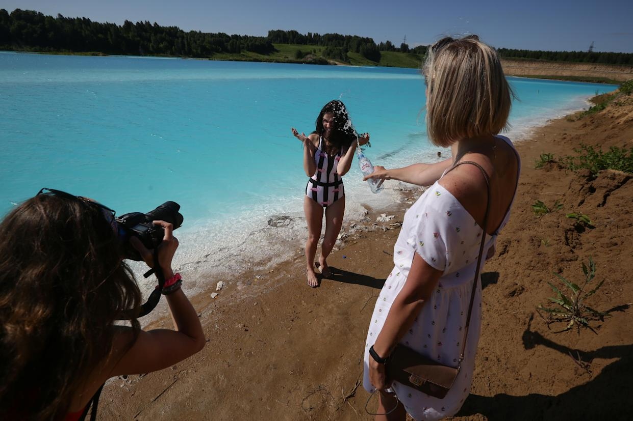 """A young woman poses for pictures by a Novosibirsk energy plant's ash dump site - nicknamed the local """"Maldives"""" - on July 11, 2019. (Photo: Rostislav Netisov/AFP/Getty Images)"""