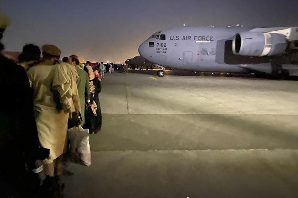 Afghan people queue up and board a U.S. military aircraft to leave Afghanistan from the military airport in Kabul on August 19, 2021 after Taliban's military takeover. (Shakib Rahmani/AFP via Getty Images)