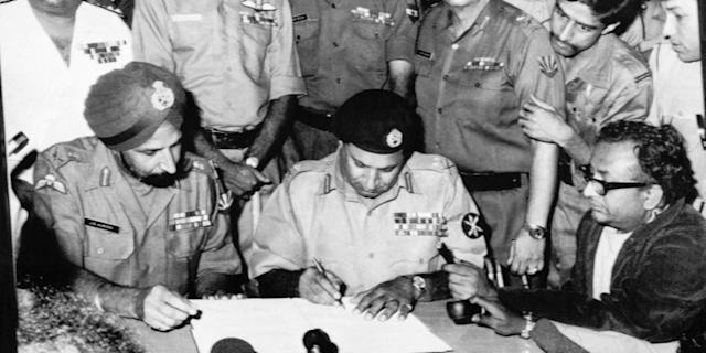 Lieutenant General A A K Niazi, Martial Law Administrator of East Pakistan, (center) signs the Surrender Document as Lieutenant General Jagjit Singh Aurora, Joint Commander of Indian and Bangladeshi Forces, (left) looks on December16, 1971 in Bangladesh. (AP Photo)