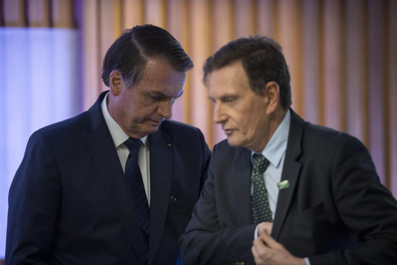 Brazilian President Jair Bolsonaro (L) and Rio de Janeiro's Mayor, Marcelo Crivella attend a ceremony at the Federation of Industries of Rio de Janeiro (FIRJAN) headquarters in Rio de Janeiro on May 20, 2019. (Photo by MAURO PIMENTEL / AFP) (Photo credit should read MAURO PIMENTEL/AFP via Getty Images)