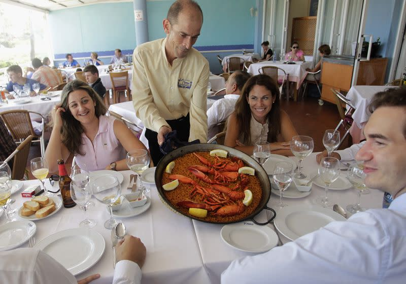 A waiter serves a traditional paella at a beach-side restaurant in Valencia, July 24, 2014. REUTERS/Heino Kalis